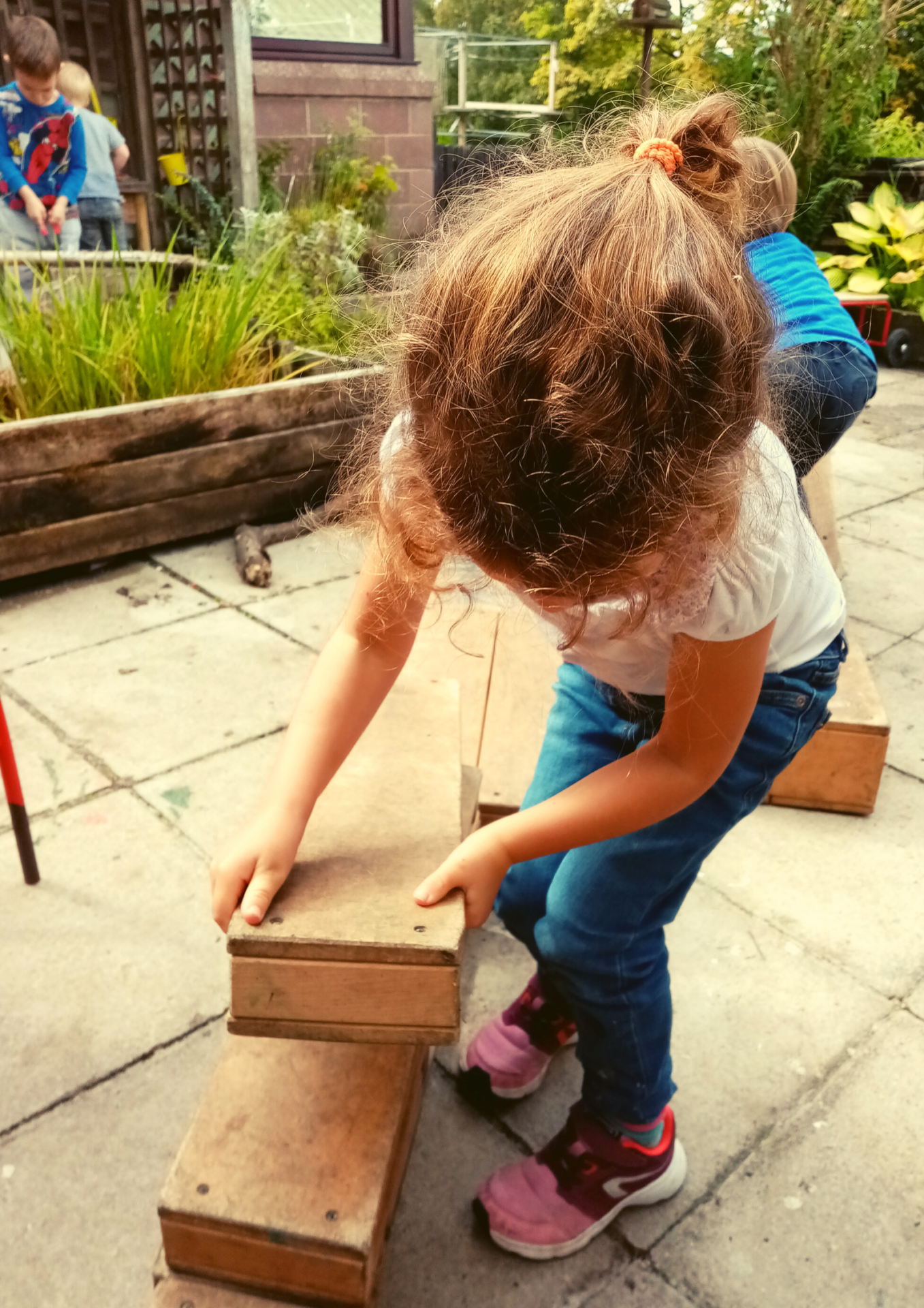 Ardvreck Nursery child fixing bench outdoors play in Crieff